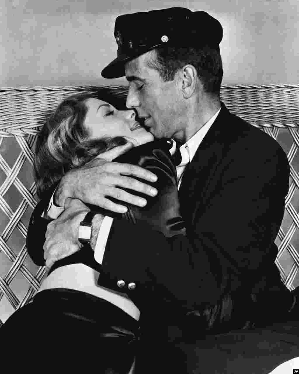 "Actor Humphrey Bogart holds actress Lauren Bacall in a tight embrace in their film ""To Have and Have Not"", in their first appearance on the screen, January 14, 1957."