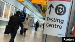 Pelancong melewati penunjuk arah menuju pusat tes COVID-19 di Bandara Heathrow, London, Inggris, 13 Februari 2021.