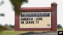 نوشته مقابل کلیسا می گوید: «آمریکا: عاشقش باش یا ترکش کن»