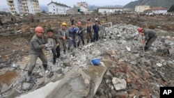 FILE - Workers recover cement blocks from flood-damaged areas in Onsong, North Hamgyong Province, North Korea, Sept. 16, 2016. Amid recent nuclear tensions, Pyongyang is struggling to secure aid for victims of flooding that occurred earlier this month.