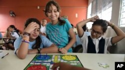 In this Friday, Oct. 13, 2017 photo, girls play a board game at the Ramon Marin Sola Elementary School, which opened its doors as a daytime community center after the passing of Hurricane Maria in Guaynabo, Puerto Rico. (AP Photo/Carlos Giusti)
