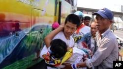 曼谷的泰國反政府抗議者把一名受傷的同伴抬上救護車。(2014年4月1日)