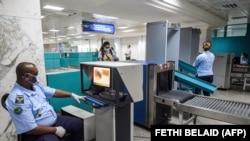 La sécurité aéroportuaire en Tunisie scanne les bagages des passagers arrivant sur le premier vol commercial international à l'aéroport international de Tunis-Carthage le 27 juin 2020, après la réouverture des frontières suivant le confinement du au COVID-19. AFP/ FETHI BELAID