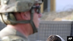 An Afghan girl stands near a U.S. soldier standing guard at a U.S. military checkpoint in Kuz district in Kunar (File)