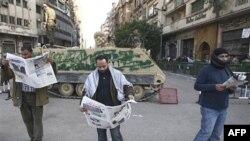 Người biểu tình chống chính phủ đọc báo phía trước một chiếc xe bọc thép ở Quảng trường Tahir ở thủ đô Cairo, ngày 2/2/2011