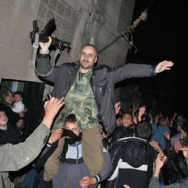 Anti-Syrian regime protesters hold up a Syrian army defector as they chant slogans against Syrian President Bashar Assad during an evening protest, in the Rastan area in Homs province, central Syria, on Monday Jan. 30, 2012.