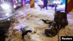 Women's shoes lay abandoned on the snow following the evacuation of a club after a fire broke out in Bucharest, Romania, Jan. 21, 2017.