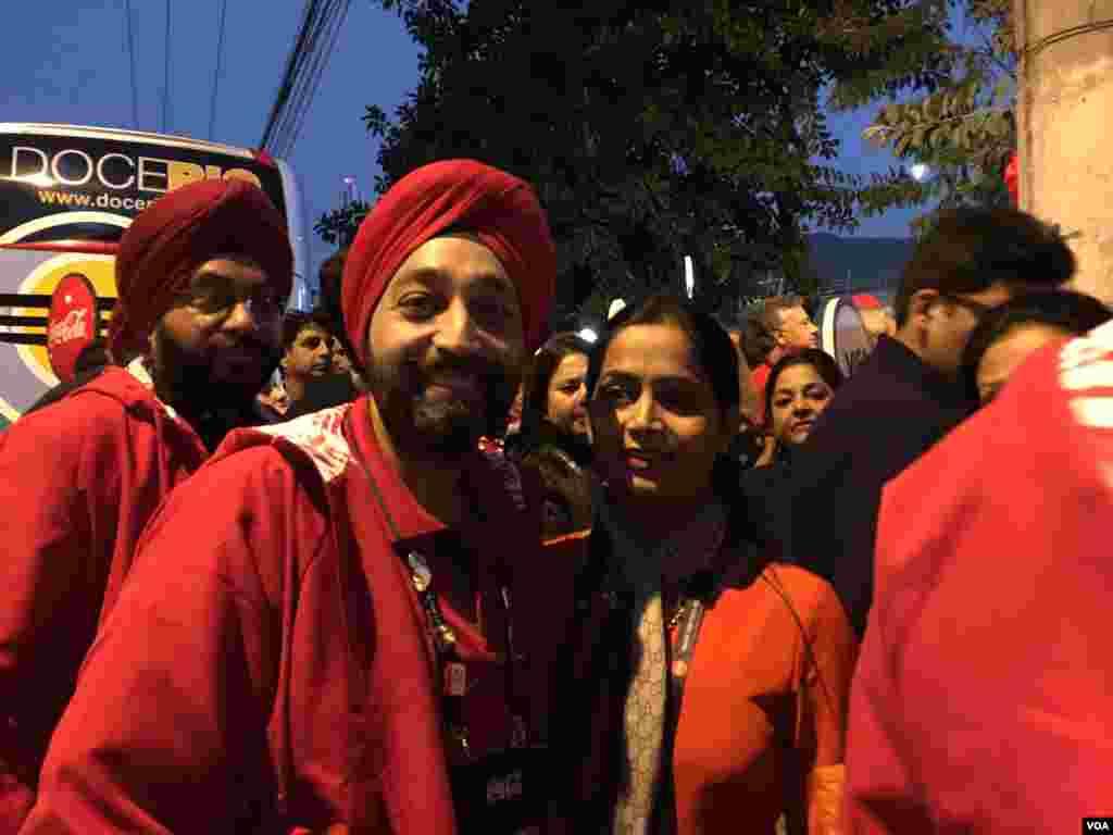 شهروندان هندی با لباس های قرمز رنگ برای تماشای مراسم افتتاح المپیک ریو به برزیل آمده اند. آنها می گویند شرکت آمریکایی کوکاکولا اسپانسر سفر آنها به ریو است.
