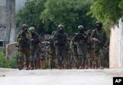 Israeli forces search for a Palestinian gunman in the village of Bruqin near the West Bank town of Salfit, March 17, 2019. The Israeli military says a Palestinian killed an Israeli and seriously wounded two others.