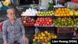 FILE - A woman sells fruit at a stand in Ho Chi Minh City.