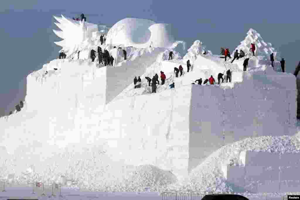 哈尔滨的一座正在雕刻的大型雪雕。一年一度的哈尔滨国际冰雪节即将开幕,准备工作正在进行。(2017年12月6日)