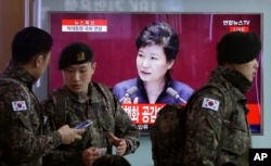 FILE - South Korean army soldiers pass by a TV screen showing the live broadcast of South Korean President Park Geun-hye's speech, at the Seoul Railway Station in Seoul, South Korea, Tuesday, Feb. 16, 2016.