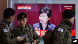South Korean army soldiers pass by a TV screen showing the live broadcast of South Korean President Park Geun-hye's speech, at the Seoul Railway Station in Seoul, South Korea, Tuesday, Feb. 16, 2016.