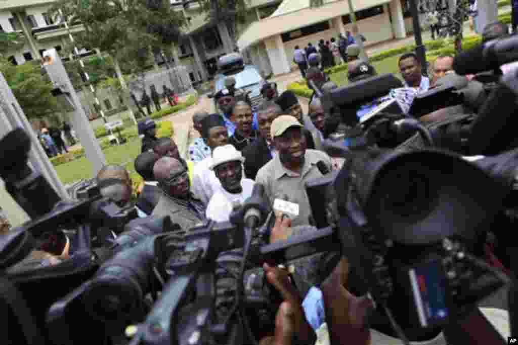 Nigeria's president Goodluck Jonathan, center right, fields questions from journalists as he leaves U.N. headquarters, where a day earlier a suicide bomber crashed through an exit gate and detonated a car full of explosives, in Abuja, Nigeria Saturday.