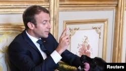 Le président français Emmanuel Macron joue avec son chien au Palais de l'Elysée à Paris, France, 30 août 2017.