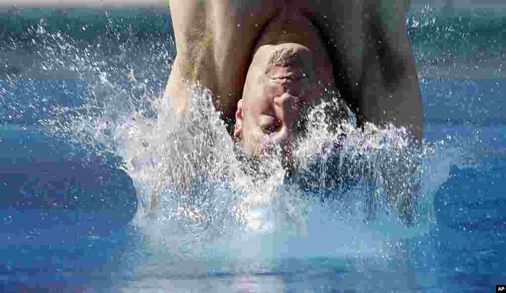 Dwight Dumais hits the water as he competes in the preliminary round of the men's 3-meter springboard event at the USA Diving Grand Prix in Fort Lauderdale, Florida.