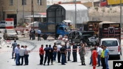 Lebanese army and plainclothes policemen gather at the site of an explosion near a police checkpoint in the eastern town of Dahr el-Baidar, Lebanon, June 20, 2014.