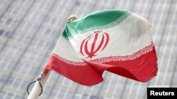 FILE - The Iranian flag flutters in front the International Atomic Energy Agency's headquarters in Vienna, July 10, 2019.