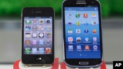 File - Samsung Electronics' Galaxy S III (R) and Apple's iPhone 4S displayed at a mobile phone shop in Seoul, South Korea, Aug. 24, 2012.