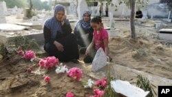 Bà Abir Shamaleh ngồi cạnh ngôi mộ của con trai bị thiệt mạng trong cuộc không kích của Israel vào thành phố Gaza, ngày 28/7/2014.