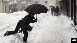 Seorang pejalan kaki harus melompati salju yang menggunung di jalanan kota Zagreb (8/12). Beberapa kawasan Eropa Tengah dan Timur dihantam badai salju dan suhu udara yang sangat dingin dalam beberapa hari terakhir ini (AP Photo/Darko Bandic)