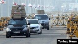 북한이 개성공단 출경을 불허한 지난 4월 입경한 개성공단 근로자들이 차량 지붕에 짐을 가득 싣고 통일대교를 건너고 있다.