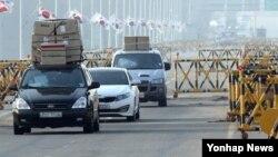 북한이 개성공단 출경을 불허한지 이틀째인 4일, 입경한 개성공단 근로자들이 차량 지붕에 짐을 가득 싣고 통일대교를 건너고 있다.