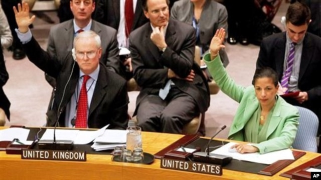 Permanent representatives from the United Kingdom, Mark Lyall Grant, left, and the United States, Susan Rice, right, vote to approve a resolution that will impose a no-fly zone over Libya during a meeting of the United Nations Security Council at UN headq
