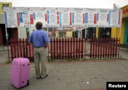 FILE - Andrzej looks at the timetable at an international bus station in Bialystok, eastern Poland, Aug. 8, 2006, before his wife leaves to work in England.
