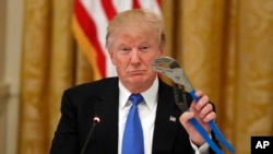 "President Donald Trump holds up a Channellock locking plier during a ""Made in America,"" roundtable event in the East Room of the White House, Wednesday, July 19, 2017, in Washington."