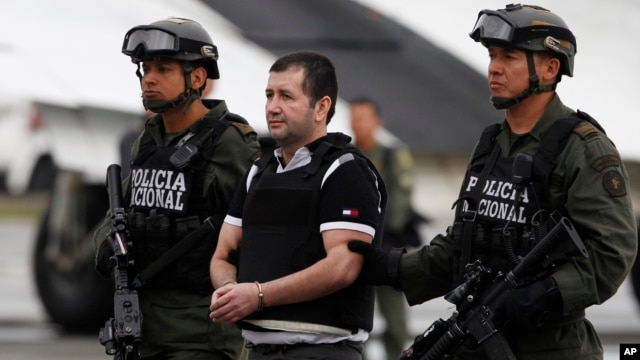 FILE - Daniel Barrera is escorted to a waiting car, prior to his extradition to the U.S, at the counternarcotics base in Bogota, Colombia, July 9, 2013.