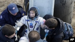 Russian space agency rescue team helps U.S. astronaut Kate Rubins to get from the capsule shortly after landing of the Russian Soyuz MS space capsule about 150 km (90 miles) southeast of the Kazakh town of Dzhezkazgan, Kazakhstan, Sunday, Oct. 30, 2016.