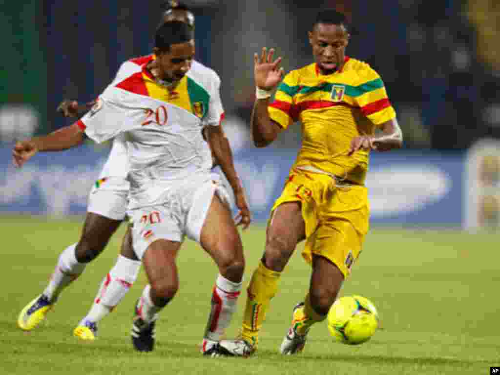 Mali's Seydou Keita challenges for the ball with Guinea's Habib Jean Balde during their African Nations Cup Group D soccer match at Franceville Stadium
