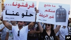 "Protesters hold up signs against the Lebanese government during a rally against the ongoing trash crisis in Beirut, Aug. 8, 2015. The sign at left reads in Arabic, ""We're sick of you, go away,"" and, at right, ""Nothing comes from you but garbage."""