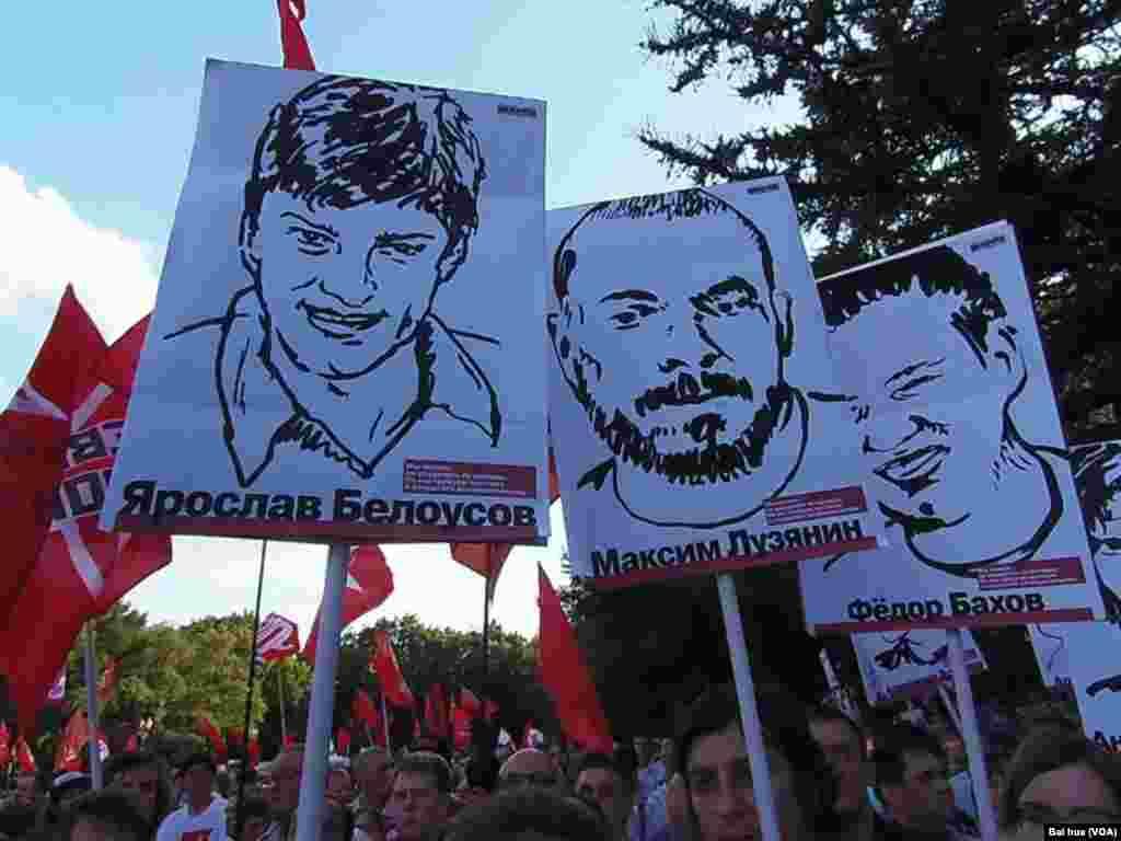 去年夏季的莫斯科反政府集会中,示威者手举被捕政治犯画像(美国之音白桦拍摄)