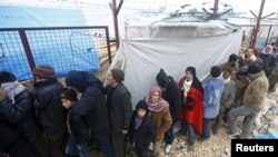 FILE - Internally displaced Syrians line up to receive blankets near the Bab al-Salam crossing, across from Turkey's Kilis province, on the outskirts of the northern border town of Azaz, Syria, Feb. 6, 2016.