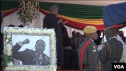 FILE: unior Shuvai Gumbochuma, sister of Zimbabwe's former first lady Grace Mugabe, speaks behind a photo of the late president Robert Mugabe, at his burial in Zvimba, Zimbabwe, Sept. 28, 2019. (C. Mavhunga/VOA)