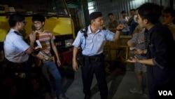 """在香港旺角商業區的一場本土派示威中,警察檢查""""本土民主前線""""的發言人黃台仰(左起第二人)的身份證(2015年6月21日)"""