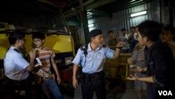 """在香港旺角商业区的一场本土派示威中,警察检查""""本土民主前线""""的发言人黄台仰(左起第二人)的身份证(2015年6月21日)"""