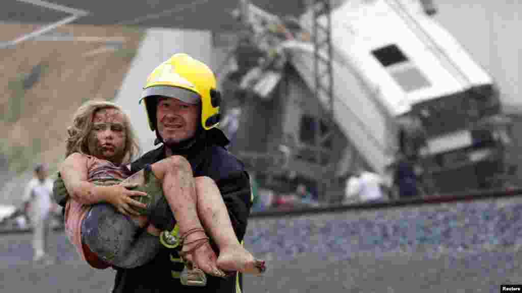 A fireman carries a wounded victim from the wreckage of a train crash near Santiago de Compostela, northwestern Spain, July 24, 2013. A train derailed outside the ancient northwestern Spanish city of Santiago de Compostela on Wednesday evening, killing at least 77 people and injuring up to 131 in one of Europe's worst rail disasters.