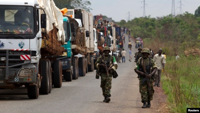 FILE - African Union peacekeepers guard a commercial convoy making its way to the border of Cameroon, near Bangui, Central African Republic, March 8, 2014.