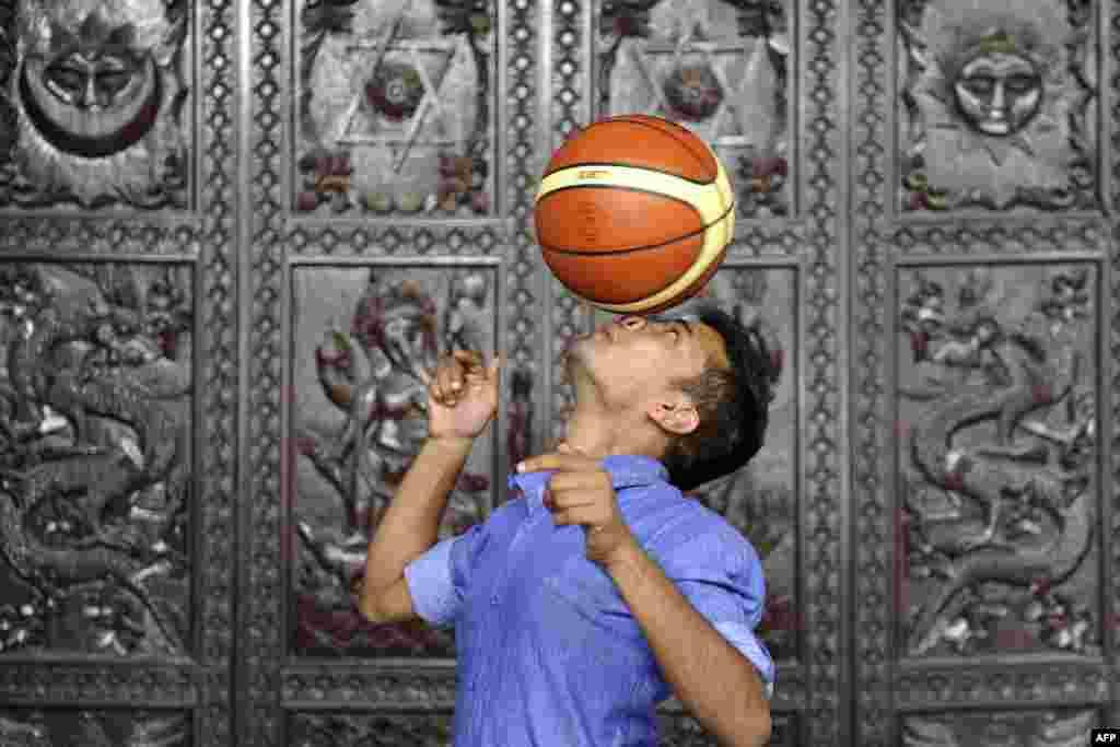 네팔 카트만두의 23세 남성이 기네스북 기록 갱신에 도전한 가운데, 7초 동안 농구공을 코 위에 올려놓고 돌리고 있다.