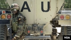 Seorang tentara Uganda yang bergabung dalam Misi Uni Afrika di Somalia (AMISOM) berpose di depan kendaraan lapis baja di wilayah Yaaqshiid, Mogadishu utara (File: dok)