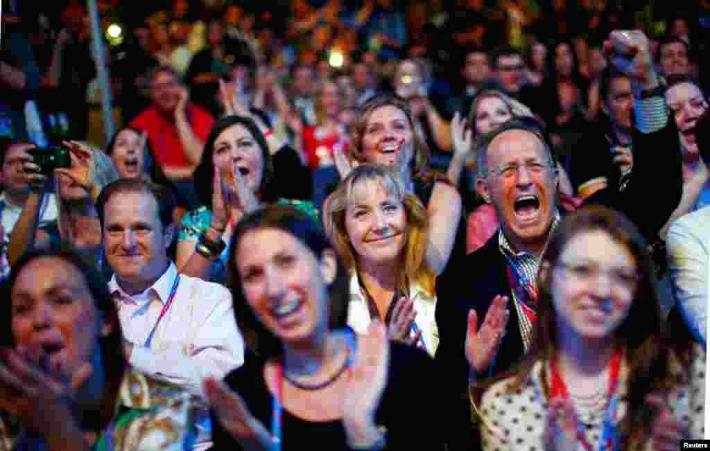 Os delegados comemoram quando vêem a imagem de Mitt Romney aparecer durante a sessão de abertura