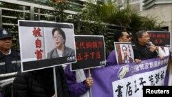 香港民主抗議者舉著銅鑼灣書店老板桂民海(左)和李波(右)的肖像(2016年1月19日)。
