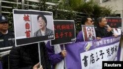 香港民主抗议者举着铜锣湾书店老板桂民海(左)和李波(右)的肖像(2016年1月19日)。