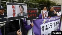 香港民主抗議者舉著銅鑼灣書店老闆桂民海(左)和李波(右)的肖像(2016年1月19日)