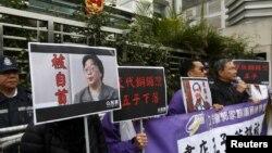 香港民主抗议者举着铜锣湾书店老板桂民海(左)和李波(右)的肖像。(2016年1月19日)