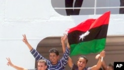 Young men in Benghazi celebrate their evacuation from Tripoli by the International Committee of the Red Cross, June 24 2011