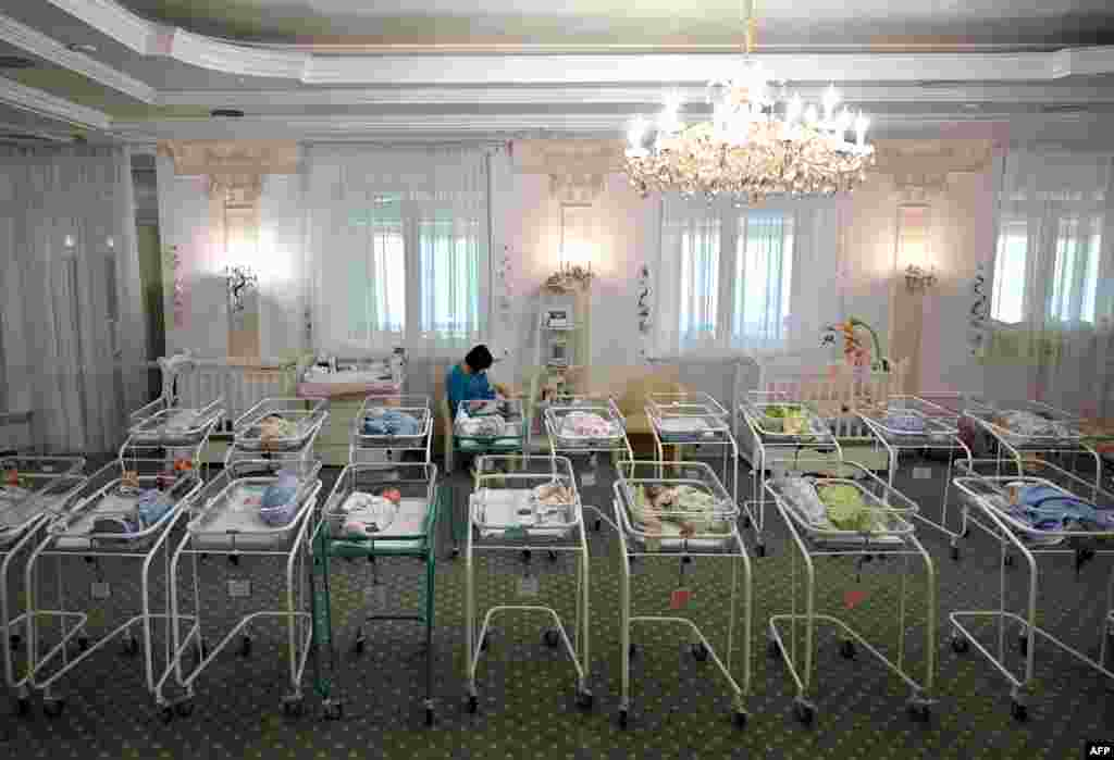 A nurse cares for newborn babies at Kyiv's Venice hotel in Ukraine. More than 100 babies born to surrogate mothers have been stranded in Ukraine as their foreign parents cannot collect them due to border closures imposed during the coronavirus pandemic.